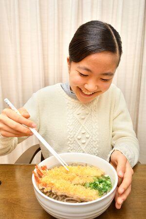 Japanese girl enjoys having buckwheat noodle with deep fried shrimp