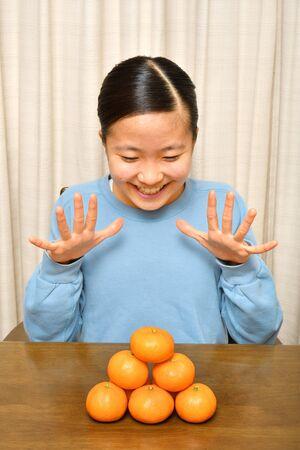 Japanese girl enjoys having mandarin orange