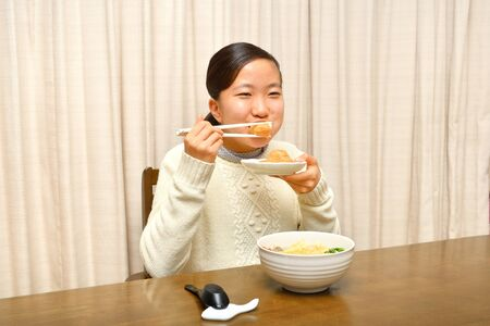 Japanese girl enjoys having buckwheat noodle with deep fried shrimp