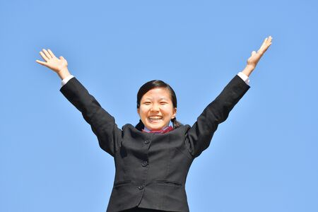 Japanese girl raising hands in the blue sky