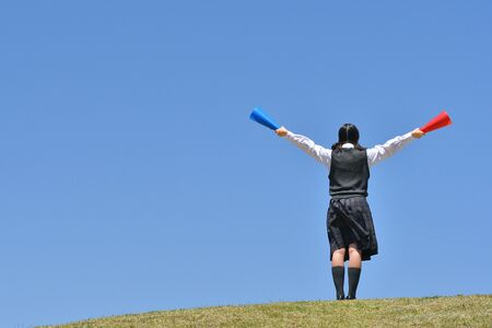 Japanese girl cheering in the blue sky rear view