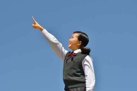 Japanese girl pointing in the blue sky