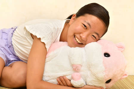 Japanese girl playing with stuffed toy on the Japanese room