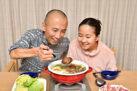Japanese girl and her father enjoying Nabe party 스톡 콘텐츠