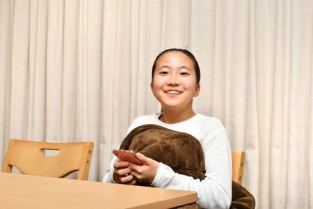 Japanese girl relaxing in the Kotatsu using smartphone