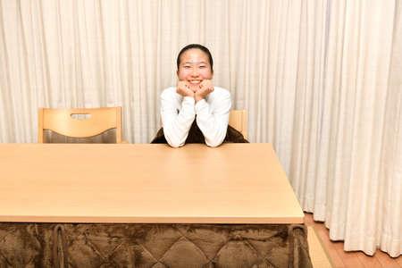 Japanese girl having a warm in the Kotatsu 스톡 콘텐츠