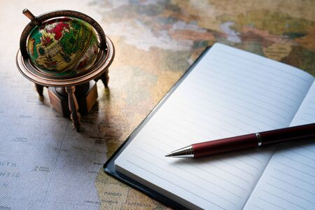 Business notebook with small globe on map background