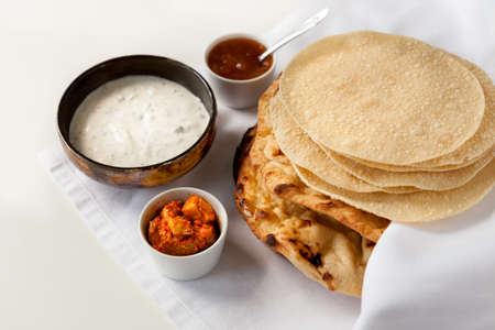Fresh Indian flat breads poppadums and naans served with mango chutney, pickle and raita on the table