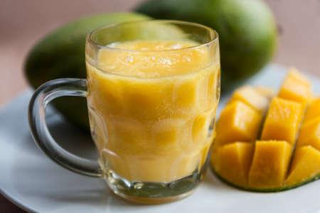 mango fruta: El vaso de batido de mango con mangos maduros