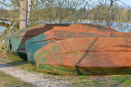 fishing fleet: old metal boat on the shore of the pond, South Bohemia, Czech Republic