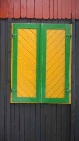 colored shutters on a wooden house, South Bohemia, Czech Republic