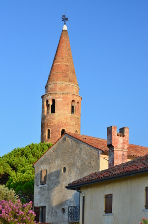 The main art gem of Caorle is the Dome of 1038 with its cylindrical bell tower conical peak, Caorle, Italy Redakční