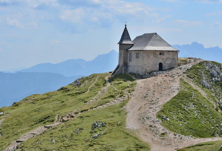 The church of Maria am Stein, the mountain Dobratsch (or Villacher Alpe, 2166 m above sea level) in the Austrian state of Carinthia. It forms the eastern tip of the Gailtal Alps and is located to the west of Villach. Austria Reklamní fotografie - 110991495