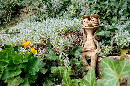 Ceramic statue of waterman sitting upon the garden pond in the middle of the blooming flowers, Marsh Marigold (Caltha palustris) flower next to him. Springtime nature of Central Europe.