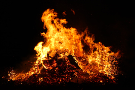 Large bonfire, burning and glowing with soft flames, sparkles flying agains the dark sky. Glowing wood silhouettes. Walpurgis night, traditional witch burning and spring welcoming ritual. 30 April. Фото со стока - 122030379