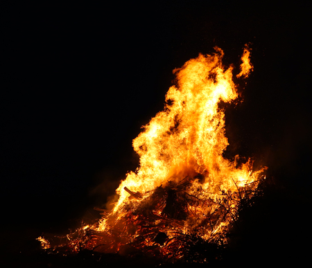 Large bonfire, burning and glowing with soft flames, sparkles flying agains the dark sky. Glowing wood silhouettes. Walpurgis night, traditional witch burning and spring welcoming ritual. 30 April. Фото со стока - 122030383