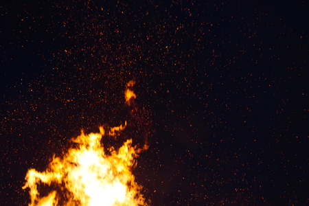 Large bonfire, burning and glowing with soft flames, sparkles flying agains the dark sky. Walpurgis night, traditional witch burning and spring welcoming ritual in the Czech Republic, April 30.