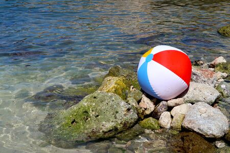 Inflatable beach ball on the rock beach in Italy with sea in the background - summer holiday vacations concept - Italy, Monopoli, Adriatic Sea