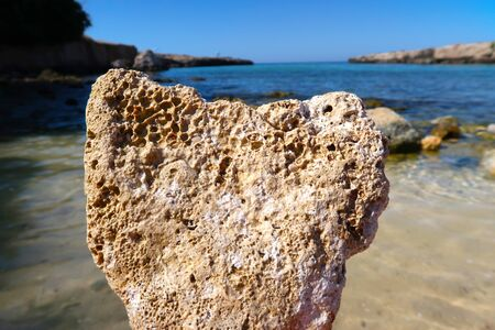 A heart shaped rock, eroded limestone with sea in the background - summer holiday vacations concept - Italy, Apulia, Monopoli, Adriatic Sea.