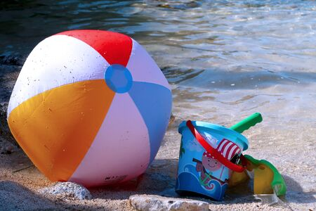 Inflatable beach ball, bucket, shovel and diving goggles on the beach in Italy with sea in the background - summer holiday vacations concept - Italy, Monopoli, Adriatic Sea Stockfoto