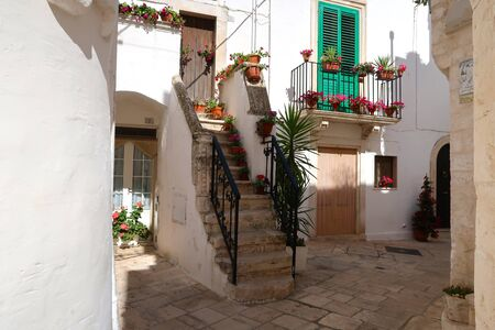 Street in Locorotondo town, Italy, region of Apulia, Adriatic Sea - entrance to the houses with stairway and balcony full of flowers