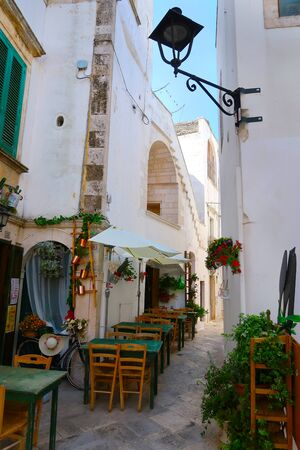 Street in Locorotondo town, Italy, region of Apulia, Adriatic Sea - a reastaurant awaiting first guests for lunch Banque d'images