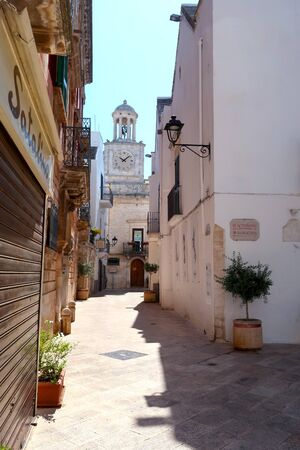 Street in Locorotondo town, Italy, region of Apulia, Adriatic Sea with clock tower in the background