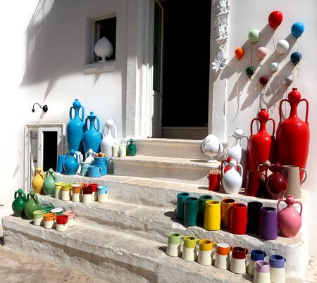 Pottery shop in Locorotondo town, Italy, region of Apulia, Adriatic Sea - colorful pots and souvenirs on the stairs in the street