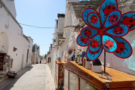 The traditional Trulli houses in the street of Alberobello city, Italy, Apulia region, Adriatic Sea with typical souvenir shop with pinwheel on the foreground