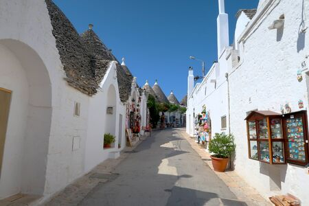 The traditional Trulli houses in the street of Alberobello city, Italy, Apulia region, Adriatic Sea with typical souvenir shops