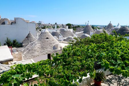Cityscape over the traditional rock roofs of the traditional Trulli houses in the streets of Alberobello city, Italy, Apulia region, Adriatic Sea