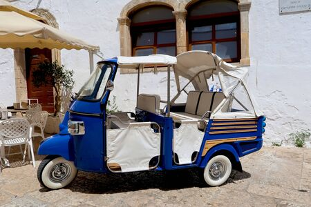Tuk-tuk, small car used mainly for tourists, standing in the street of Ostuni town, Apulia region, Italy, Adriatic Sea
