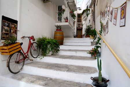 Street of Ostuni town with staircase full of blooming flowers, Apulia region, Italy, Adriatic Sea Stockfoto - 139228310