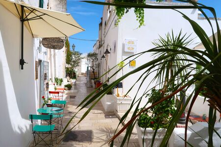 Scenic sight of the Ostuni town sunny street with typical restaurants and blooming flowers, Apulia region, Italy, Adriatic Sea