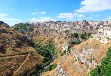 View at the ancient town of Matera (Sassi di Matera), with its Gravina river canyon and typical medieval cave dwellings, Basilicata, southern Italy Фото со стока