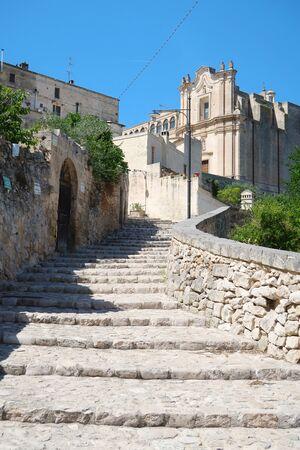 Sunny street of ancient town of Matera (Sassi di Matera) with stone steps, Basilicata, southern Italy
