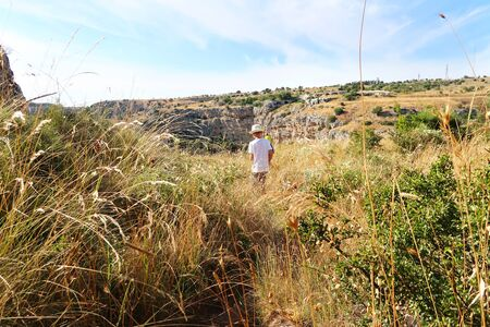Tourists walking in the high grass towards the typical medieval cave dwellings in the countryside near the ancient town of Matera (Sassi di Matera), Basilicata, southern Italy