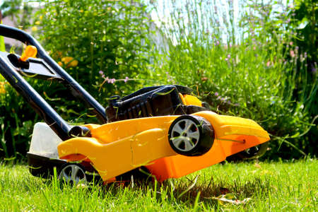 Yellow kids' lawn mower toy pretending to cut the grass