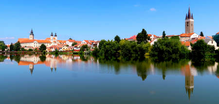View of Telc town across the lake with reflections of the buildings in the water