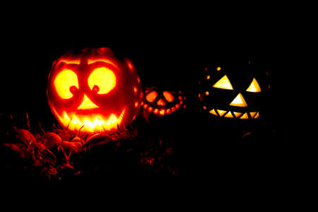 Three Halloween pumpkins glowing in the night.