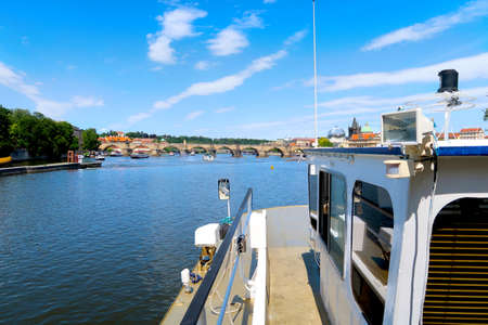 River Vltava with Charles Bridge in the background view from the deck of the tourist boat, sightseeing cruise in Prague, Czech Republic, boheman region.