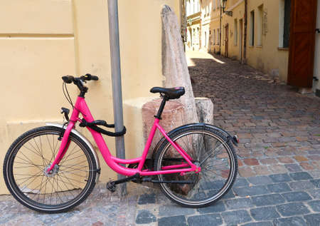 Pink bicycle leaning against the wall in the street of Prague city, Czech Republic, a typical street of the old town in the background. It is locked to the lamppost. Фото со стока