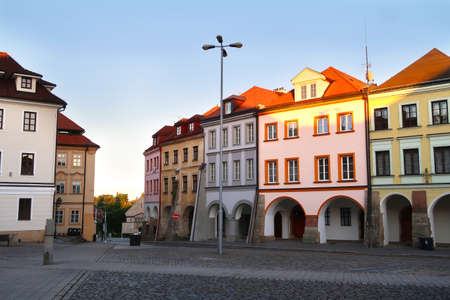 Small Square (Male namesti) in Hradec Kralove city, Czech Republic, bohemian region with its typical historical archway buildings. Dusk in the city. Фото со стока