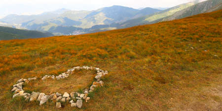 Landscape scenery. Stone heart on the meadow with view of the Low Tatras (Nizke Tatry) on the tourist path to the Chopok mountain peak. Summertime in the Northern Slovakia, Slovak Republic, Europe. Stockfoto