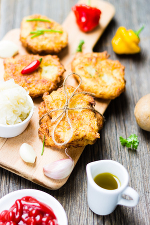 Food. Potato Pancakes on Breadboard with Ingredients on Wooden Background