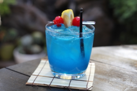 Blue Hawaiian speicalty cocktail with cherry pineapple garnish, outside with bamboo coaster