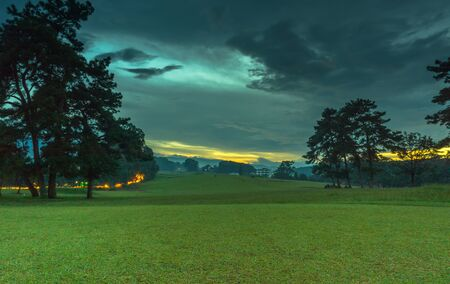 Light trails with sunset at the background at golf course