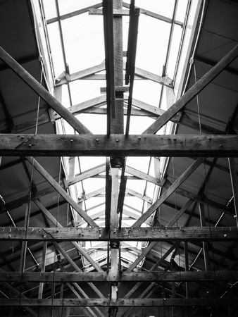 roof framework: Monochrome old wooden factory roof framework structure with lit Stock Photo