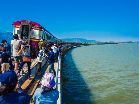 Tourists taking photograph near vintage train on railway at Pasak Jolasit Dam
