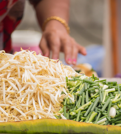 bean sprouts: Hand of street vender preparing bean sprouts and scallion for Pad Thai
